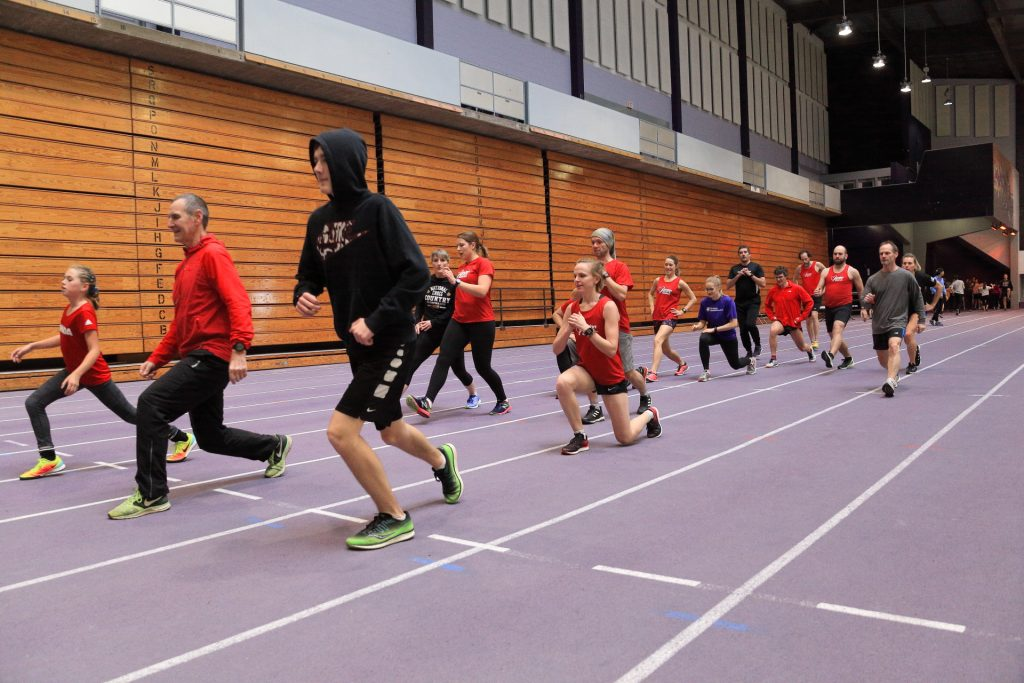 Club members running indoor track.